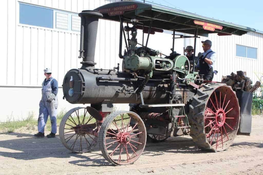 Two men operate the 35 HP Case steam traction engine while 1 man walks alongside