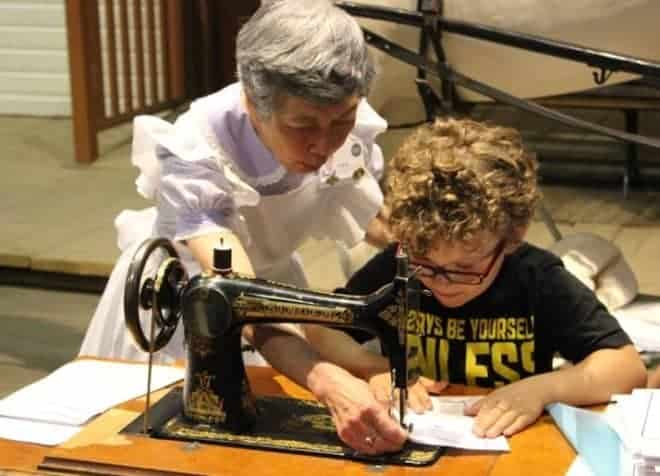 One of the Saskatchewan history activities - a woman in old fashioned dress and apron assists a young boy at a treadle sewing machine