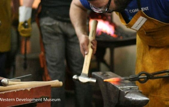 Blacksmithing student bends over the anvil, using a ball pien hammer to tap on the head of an orange hot metal punch