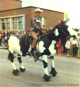 Man riding Blowtorch, the mechanical horse in a parade with people watching.