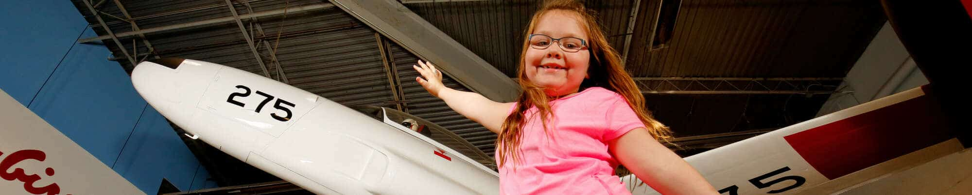Girl with arms outstretched in front of a Snowbird's jet on display in Moose Jaw.