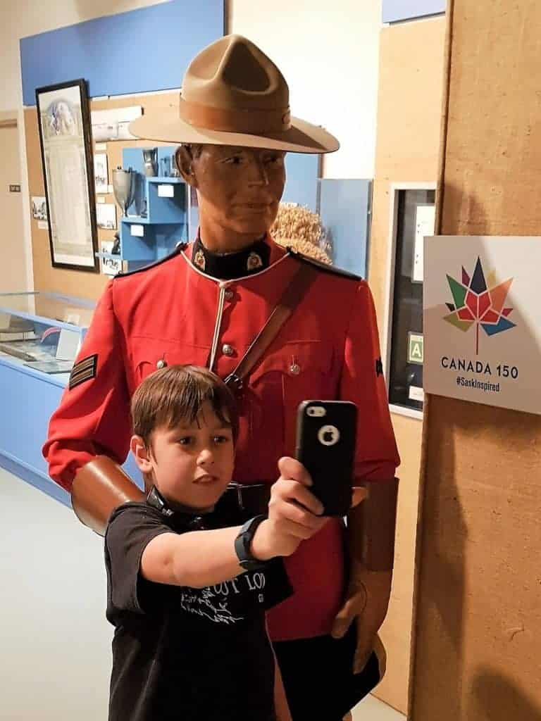Young man takes selfie in front of RCMP manequin