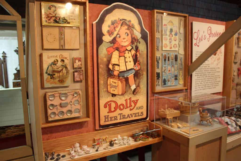 """Artifacts from Bladon Toys exhibit including a big poster featuring an old fashioned blonde """"dolly"""""""