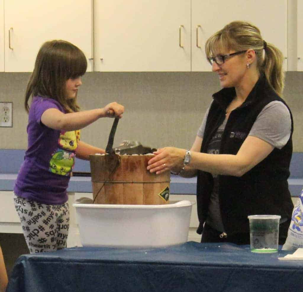 Young girl stands on chair to reach handle of hand cranked ice cream maker which is held steady by a WDM staff person