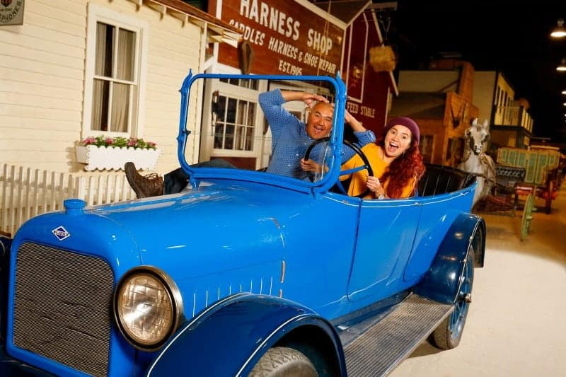 Two people pose inside the blue McLaughlin car