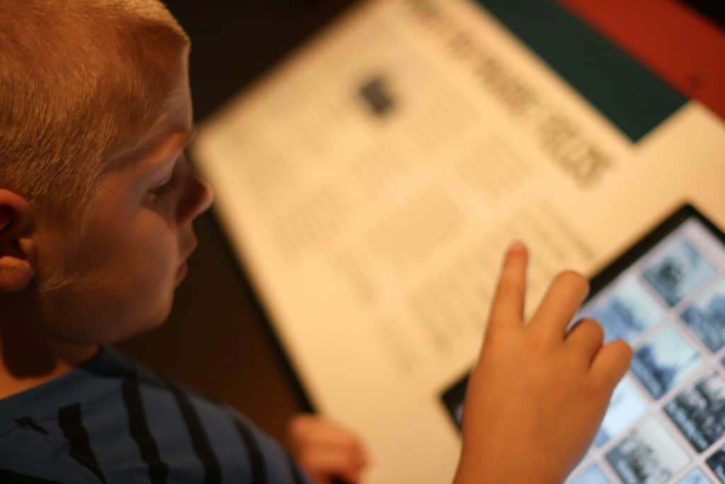 Young boy makes selections on touch screen artifact sign