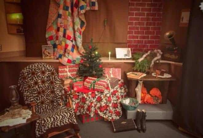 Rocking chair draped with a cozy blanket in front of a table piled with Christmas presents and a small Christmas tree and a pretend fireplace