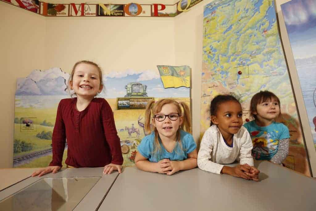 Young children sit at a table in a colourful room