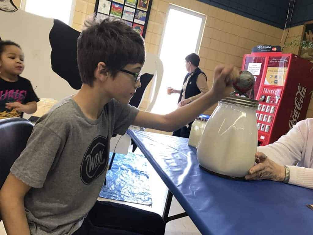 Butter-making demonstration - young boy turns hand crank on glass butter churn