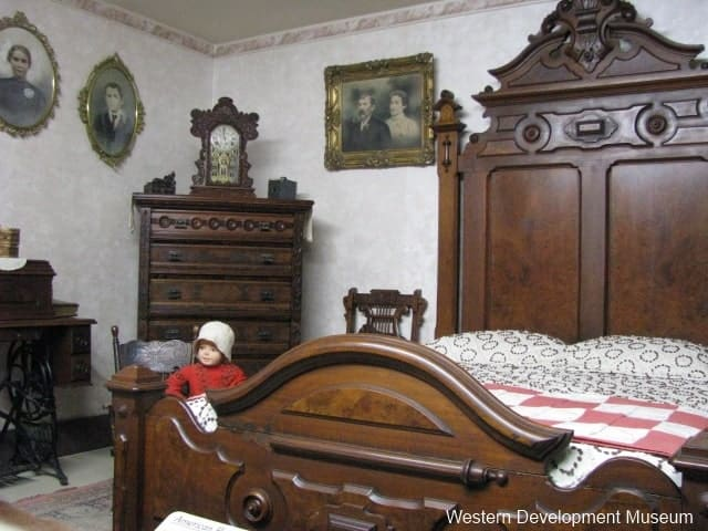 A wooden bedstead, armoire, and sewing machine set the stage for this turn of the century American bedroom