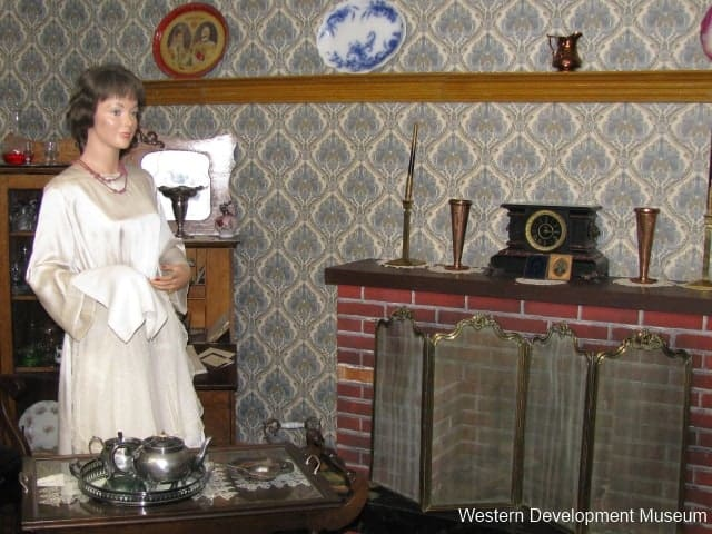 British exhibit, featuring a female mannequin standing by a brick fireplace