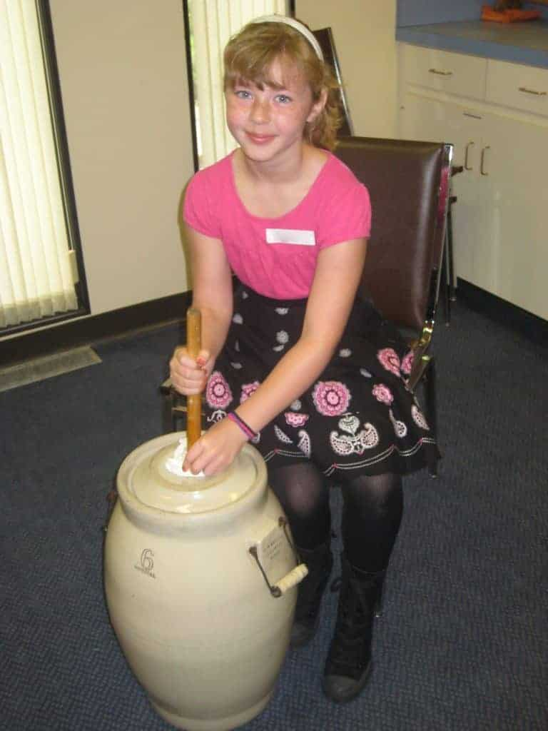 Girl participating in butter-making by hand, using a butter churn