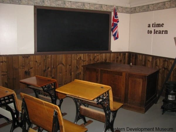 A time to learn exhibit, with old fashioned student desks, teacher desk, and blackboard