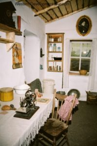 Inside the soddie, showing whitewashed wallsand a table with sewing machine ready for mending