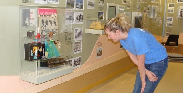 Woman examines case of 1960s popular culture artifacts, including a Barbie and a Beatles LP
