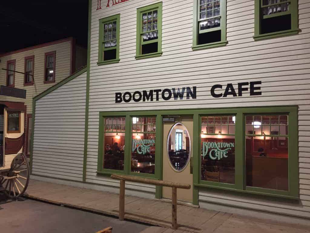 Front of Boomtown Cafe large white building, with green trimmed windows to peer into at street level and a hitching post out front.