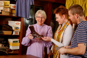 A volunteer showing a couple a lady's boot from the 19th century.