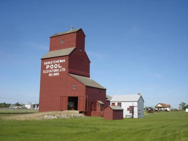 Brown-red rust coloured grain elevator, with Saskatchewan Pool Elevators Ltd. No. 889 painted in white on the side