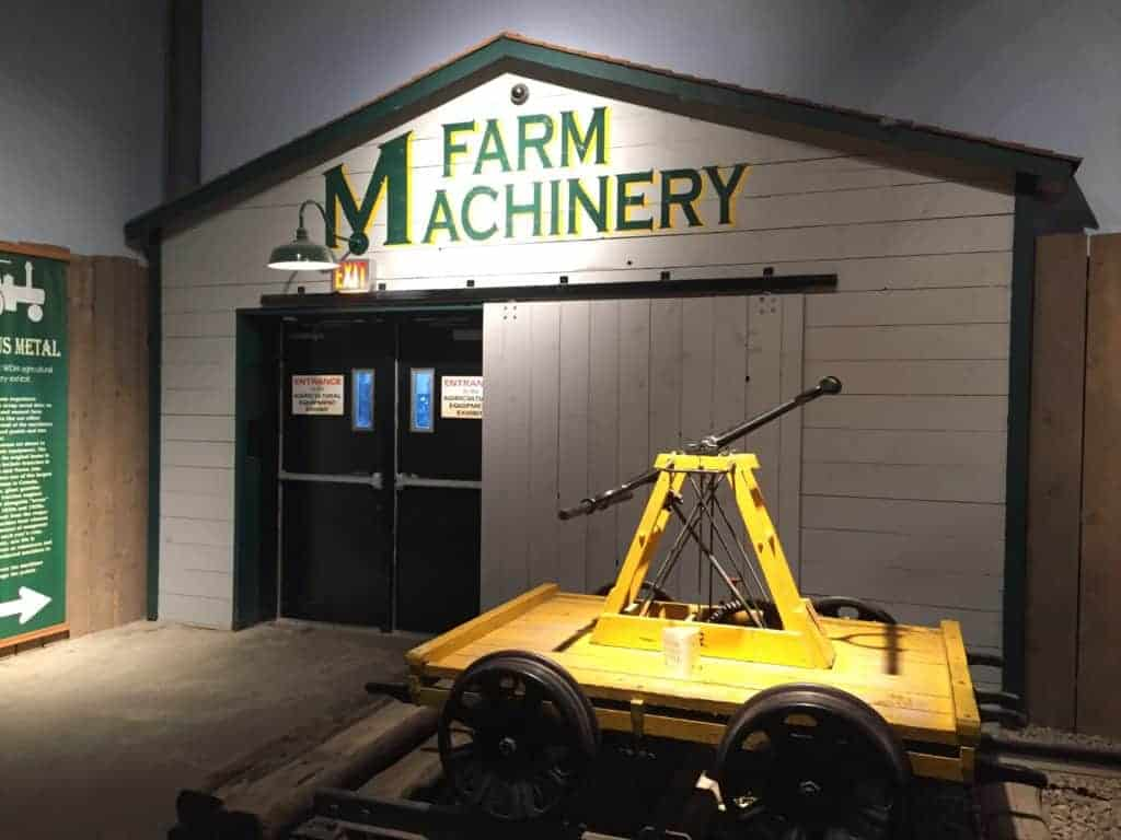 """Facade of farm quanset, with mock sliding barn door. The sign above reads """"farm machinery."""" Black doors lead to the agricultural machinery exhibit."""