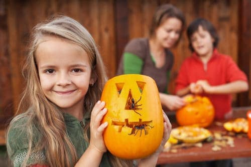 Small child holding pumpkin she has carved