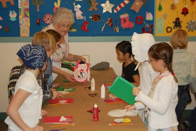 Older woman at the head of a table shows students a homemade Christmas card craft