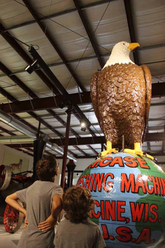 Two young boys looking up at the Case Eagle as it sits on a large globe.
