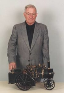 Fred Dalby stands behind his father's model steam engine