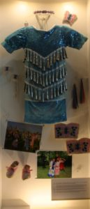 Photo of blue jingle dress with other photos , shoes and other items on display.