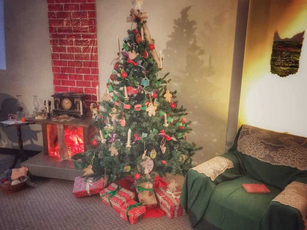 Christmas tree with wrapped presents underneath stands in front of a fireplace