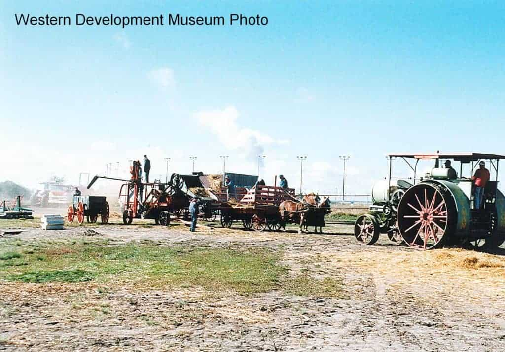 Re-enacted circa 1920s agriculture scene: Grain harvest scene, featuring a gas tractor, threshing machine, horse drawn bundle wagon