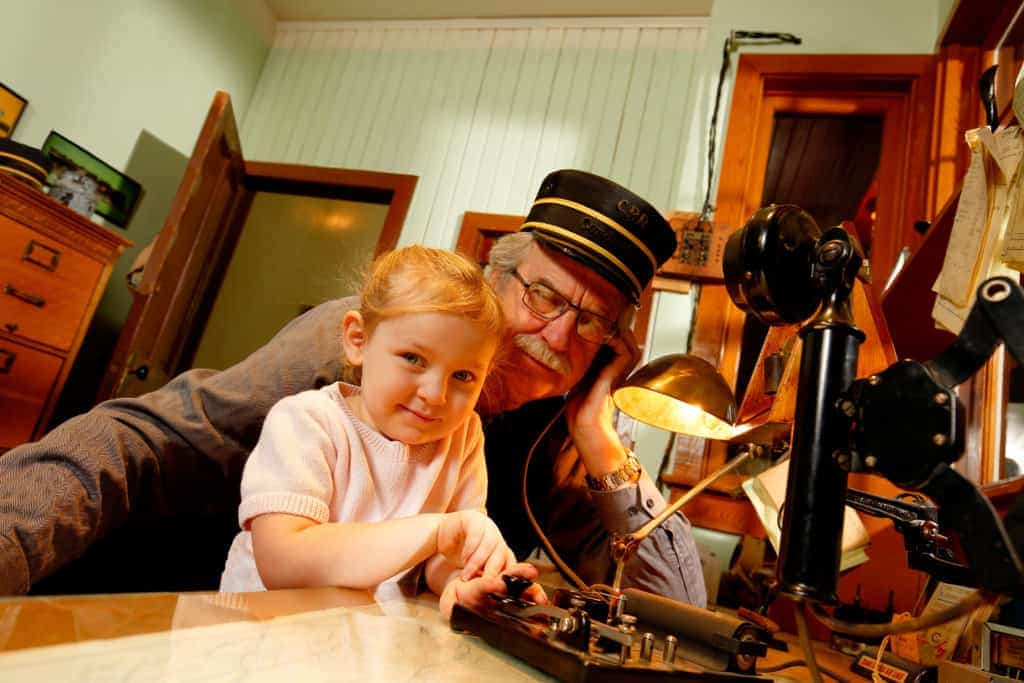 Telegrapher showing little girl in pink shirt how to communicate with a telegraph