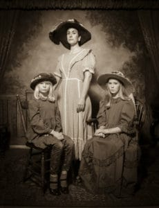 Black and white portrait of three girls in early 1900s dress