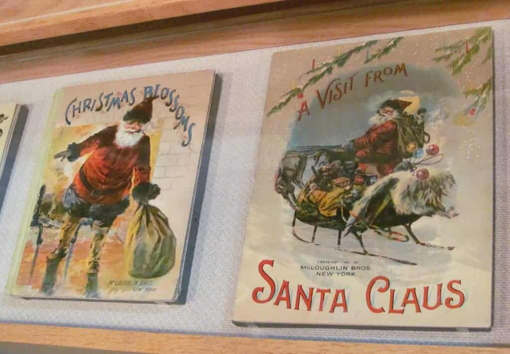 "Two early 1900s era Christmas cards. The first features Santa Claus in his sleigh with the words ""A visit from Santa Claus."" The second features Santa Clause bending over to pick up a big sack, smoking his pipe and the words ""Christmas Blossoms."""