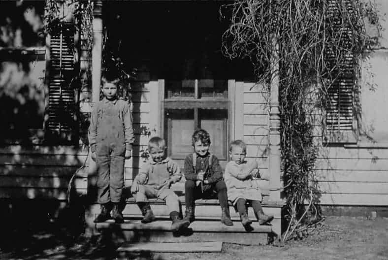 Little boys sitting on front step of house