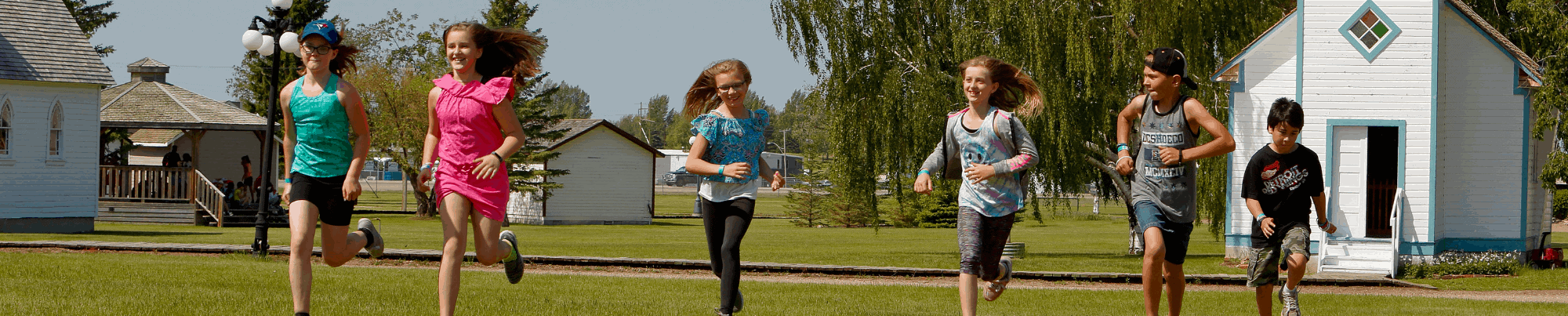 Six children running on the lawn at the Village at the WDM North Battleford