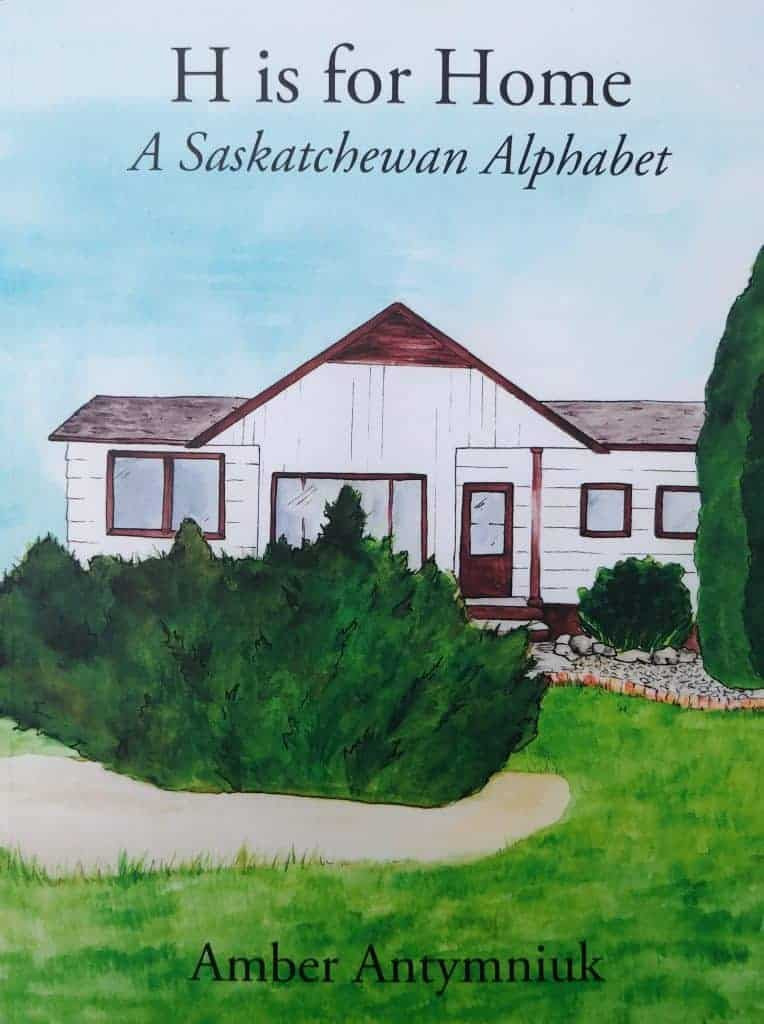 Cover of H is for Home A Saskatchewan Alphabet book featuring a white bungalow with green grass and shrubs in front of it. The author's name Amber Antymnuik is at the bottom.