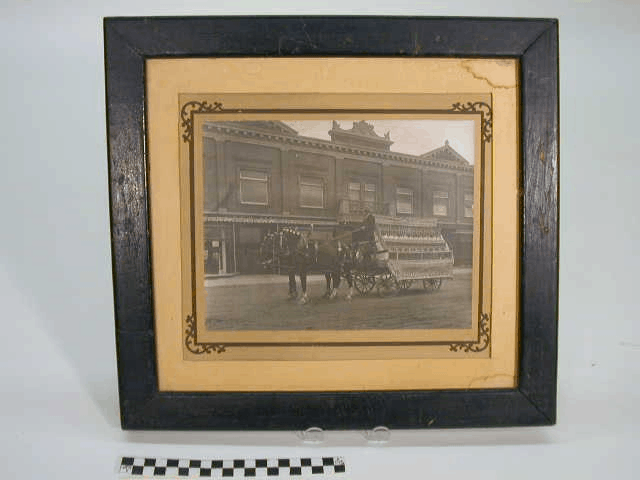 Framed black and white photo of a Silverood Springs bottled water delivery wagon pulled by two horses. Frame is black, double layered tan matting with elaborate corner designs around the photo.