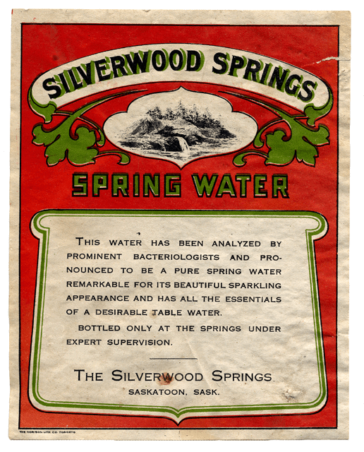 "Label from a Silverwood Springs bottle of spring water. Red background. Write banner with green fleur-de-lis like leaves hanging down from it reads ""Silverwood Springs."" Between the leaves is a black and white photo of pine trees and a stream. Below that are the words SPRING WATER in green. Below that is a white plaque like space with text reading ""This water has been analyzed by prominent bacteriologists and pronounced to be a pure spring water remarkable for its beautiful sparkling appearance and has all the essentials of a desirable table water. Bottled only at the springs under expert supervision. The Silverwood Springs Saskatoon, Sask."""