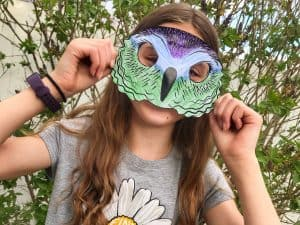 Young girl wearing a homemade paper mask in the shape of an owl face