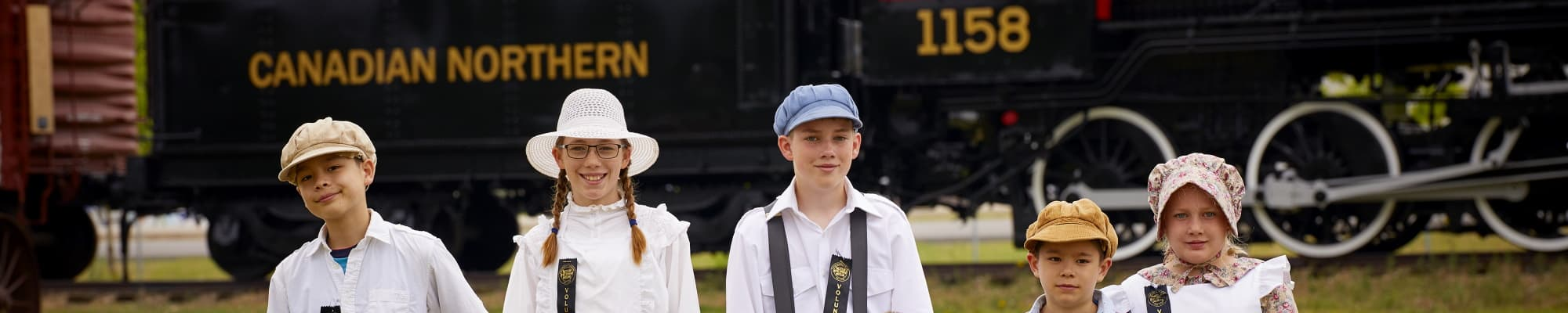5 kids, dressed in 1910 era clothing and hats standing in front of a steam locomotive